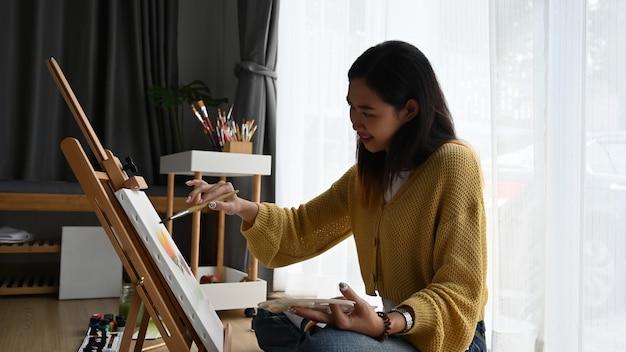 Vista lateral do pintor alegre jovem está desenhando e sentado no chão em frente a uma tela.