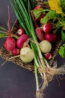 Vista lateral do prato de cesta de legumes como rabanete e cebolinha no fundo marrom com espaço de cópia