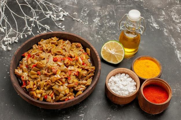 Vista lateral do prato de feijão e especiarias taças de três tipos de especiarias coloridas o prato de feijão verde ao lado dos galhos das árvores e uma garrafa de óleo na mesa escura