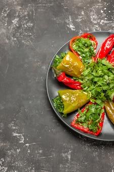Vista lateral do prato de pimentas - os apetitosos pimentões vermelhos e verdes com ervas na placa preta