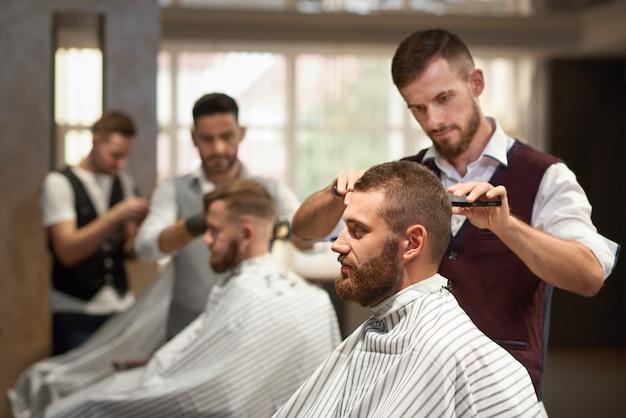 Vista lateral do processo de penteado na barbearia