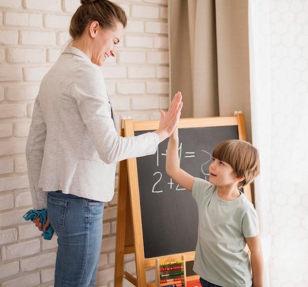 Vista lateral do professor cumprimentando a criança em casa