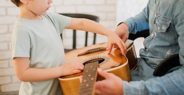 Vista lateral do professor de criança e violão