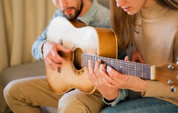 Vista lateral do professor de guitarra, ensinando alguém em casa