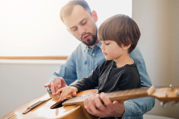 Vista lateral do professor de violão, dando lições para a criança em casa