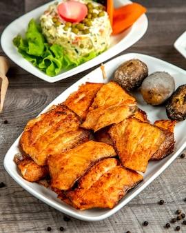 Vista lateral do quibe de esturjão com batata assada, servido com salada de legumes em uma mesa de madeira
