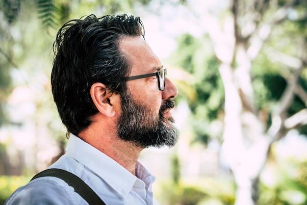 Vista lateral do retrato adulto de homem maduro com barba e óculos olhando e pensando