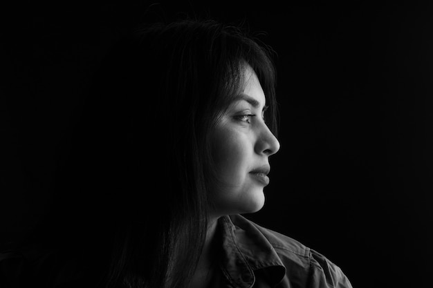 Vista lateral do retrato escuro de uma mulher latina em fundo preto, preto e branco