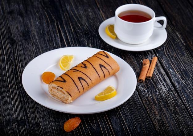 Vista lateral do rocambole com geléia de damasco em um prato branco, servido com uma xícara de chá no rústico