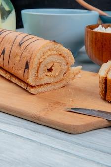 Vista lateral do rolo cortado com faca na tábua com cereais de queijo cottage com leite condensado na superfície de madeira