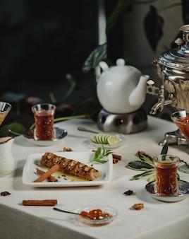 Vista lateral do rolo de biscoito cheio de nozes, servido com chá em uma mesa