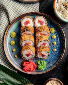 Vista lateral do rolo de sushi com caranguejo e atum em um prato com gengibre e wasabi na madeira
