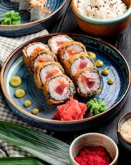 Vista lateral do rolo de sushi com caranguejo e atum em um prato com gengibre e wasabi na superfície de madeira