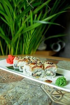Vista lateral do rolo de sushi de cozinha tradicional japonesa com enguia abacate e creme de queijo em verde