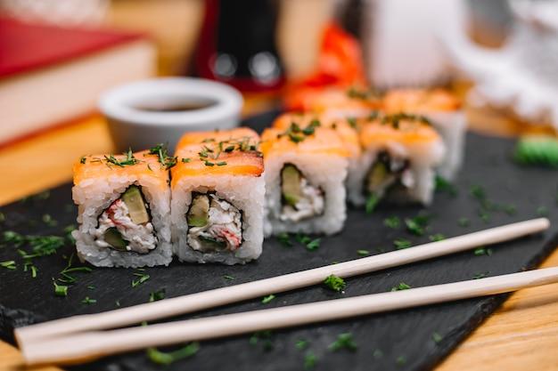 Vista lateral do rolo de sushi tradicional culinária japonesa com abacate de carne de caranguejo de salmão e creme de queijo no quadro negro