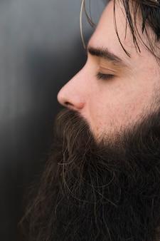 Vista lateral do rosto de um homem com os olhos fechados