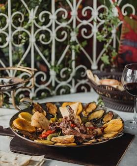Vista lateral do saj kebap com costelas de cordeiro batatas pimentões coloridos e berinjelas em uma placa de madeira em cima da mesa