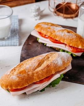 Vista lateral do sanduíche com carne e tomate em cima da mesa