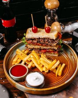 Vista lateral do sanduíche de carne com tomate, servido com batatas fritas e molhos no prato