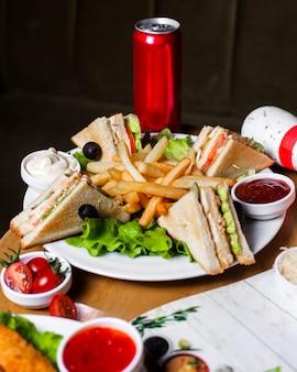 Vista lateral do sanduíche de clube com frango, batatas fritas e molhos na placa de madeira