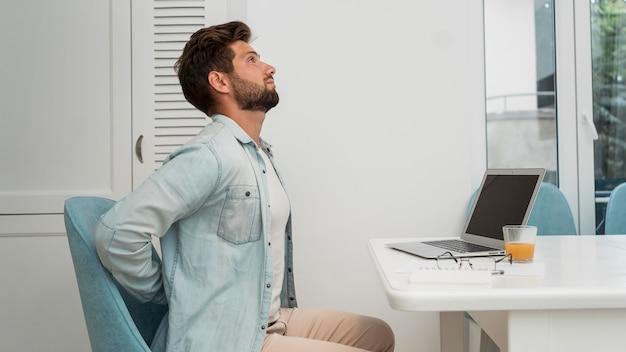 Vista lateral do sexo masculino adulto trabalhando em casa