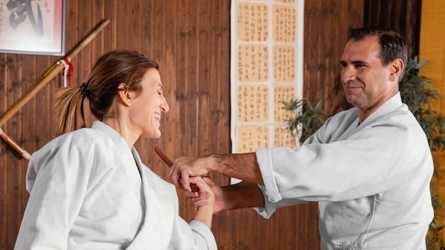 Vista lateral do sorridente instrutor de artes marciais na sala de prática com a estagiária