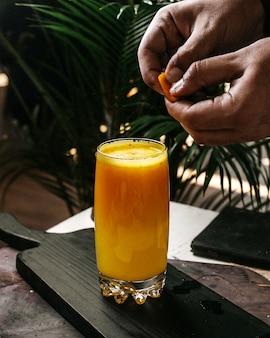 Vista lateral do suco de laranja em uma tábua de madeira