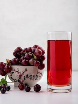 Vista lateral do suco de uva preta em um copo e uma tigela de uvas vermelhas no fundo branco