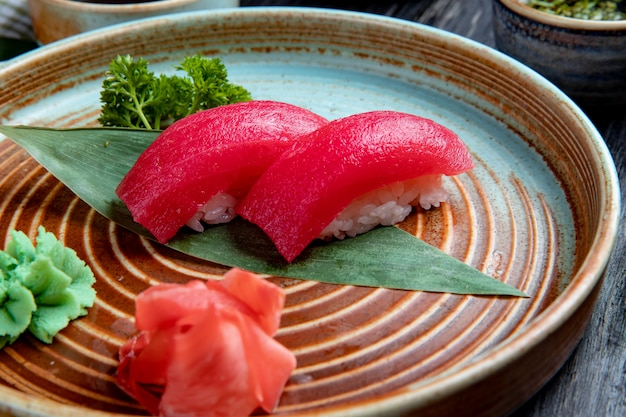 Vista lateral do sushi nigiri com atum na folha de bambu, servido com fatias de gengibre em conserva e wasabi em um prato