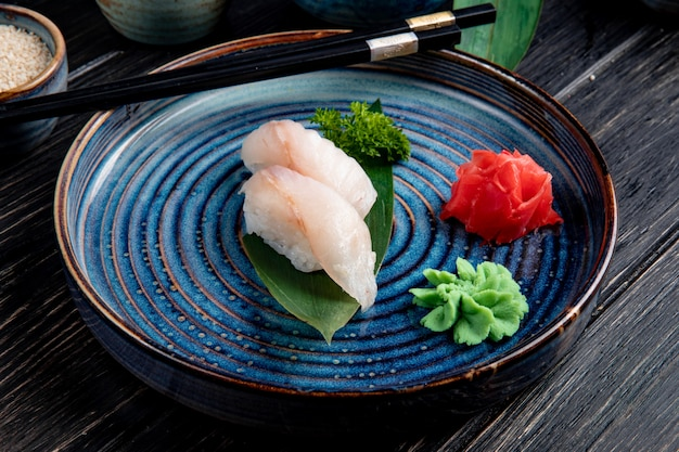 Vista lateral do sushi nigiri na folha de bambu, servido com gengibre e wasabi em um prato