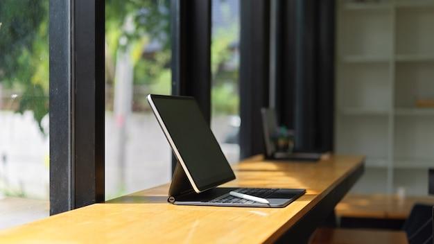 Vista lateral do tablet portátil com teclado na mesa de madeira no café