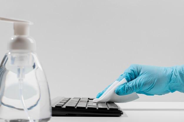 Vista lateral do teclado sendo desinfetado manualmente com luva cirúrgica