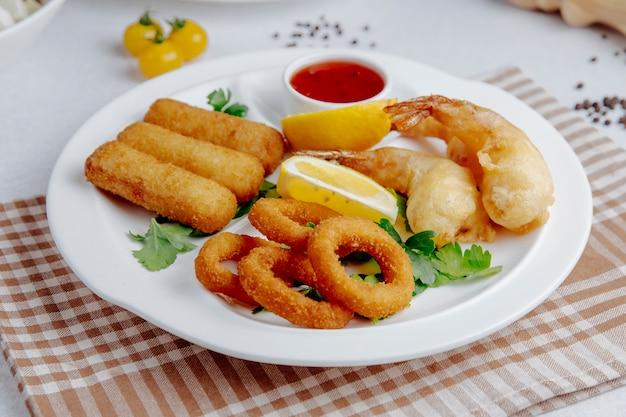 Vista lateral do tempura de lulas e camarões em um prato branco