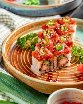 Vista lateral do tempura sushi maki com camarão e abacate em um prato com gengibre e wasabi