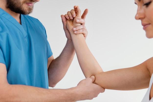 Vista lateral do terapeuta osteopático masculino verificando a articulação do cotovelo de uma paciente