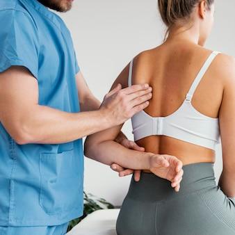 Vista lateral do terapeuta osteopático masculino verificando o osso da escápula de uma paciente do sexo feminino