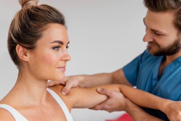 Vista lateral do terapeuta osteopático verificando o ombro de uma paciente