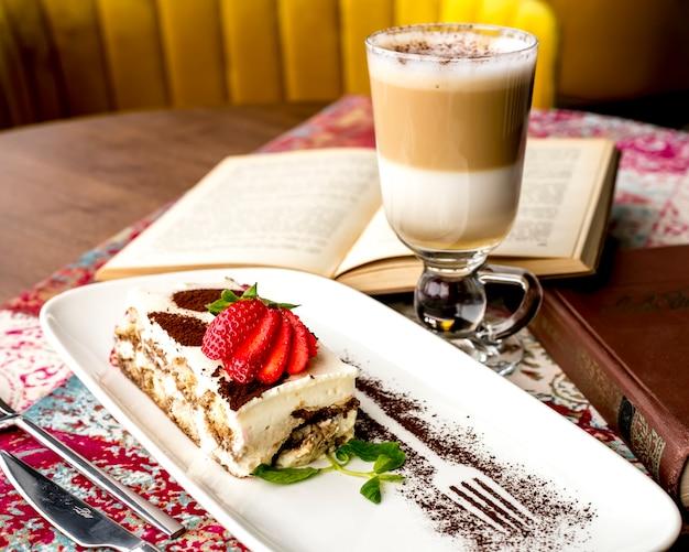 Vista lateral do tiramisu, decorado com morangos fatiados e cacau em pó em um prato, servido com um copo de café com leite em cima da mesa