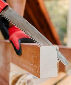 Vista lateral do trabalhador da construção civil cortando um pedaço de madeira com serra