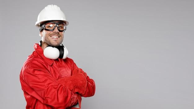 Vista lateral do trabalhador da construção civil masculino sorridente