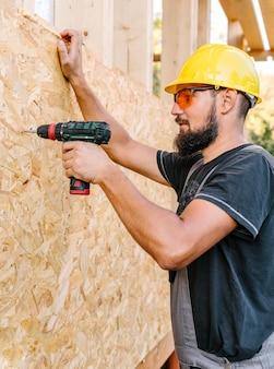 Vista lateral do trabalhador da construção civil perfurando madeira compensada