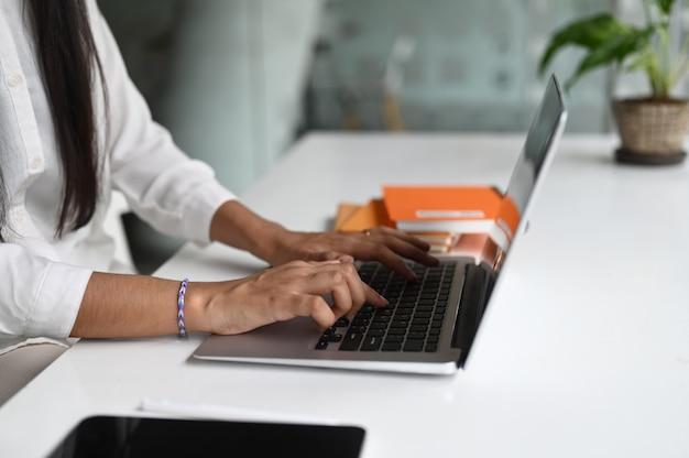 Vista lateral do trabalhador de escritório feminino trabalhando no laptop em um escritório moderno.