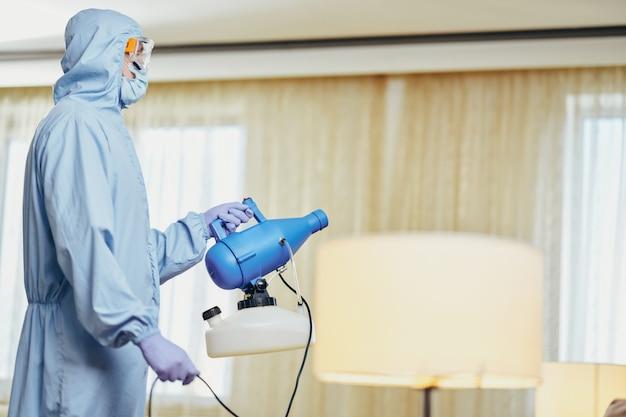Vista lateral do trabalhador prestando um serviço e fazendo a desinfecção em quarto de hotel. coronavírus e conceito de quarentena