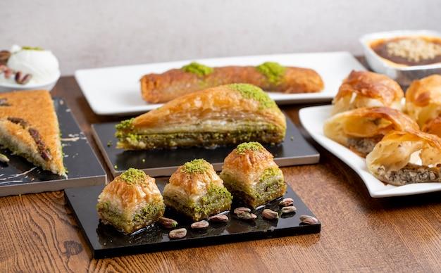 Vista lateral do tradicional baklava de sobremesa turca com pistache em uma mesa de madeira