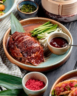 Vista lateral do tradicional comida asiática pato com pepinos e molho num prato