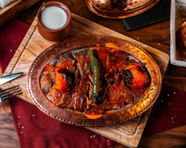 Vista lateral do tradicional iskender turco iskender com iogurte em uma panela de barro em uma placa de madeira