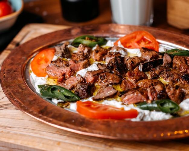 Vista lateral do tradicional iskender turco iskender com iogurte no prato
