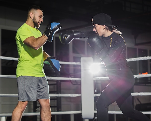 Vista lateral do treinador masculino e feminino boxeador praticando