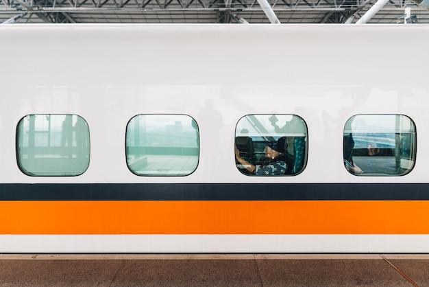 Vista lateral do trem de alta velocidade de formosa, trem branco com a listra alaranjada e azul.