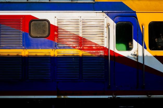 Vista lateral do trem tailandês colorido.